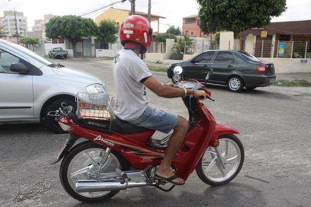 Condutor dirigindo ciclomotor em via na capital