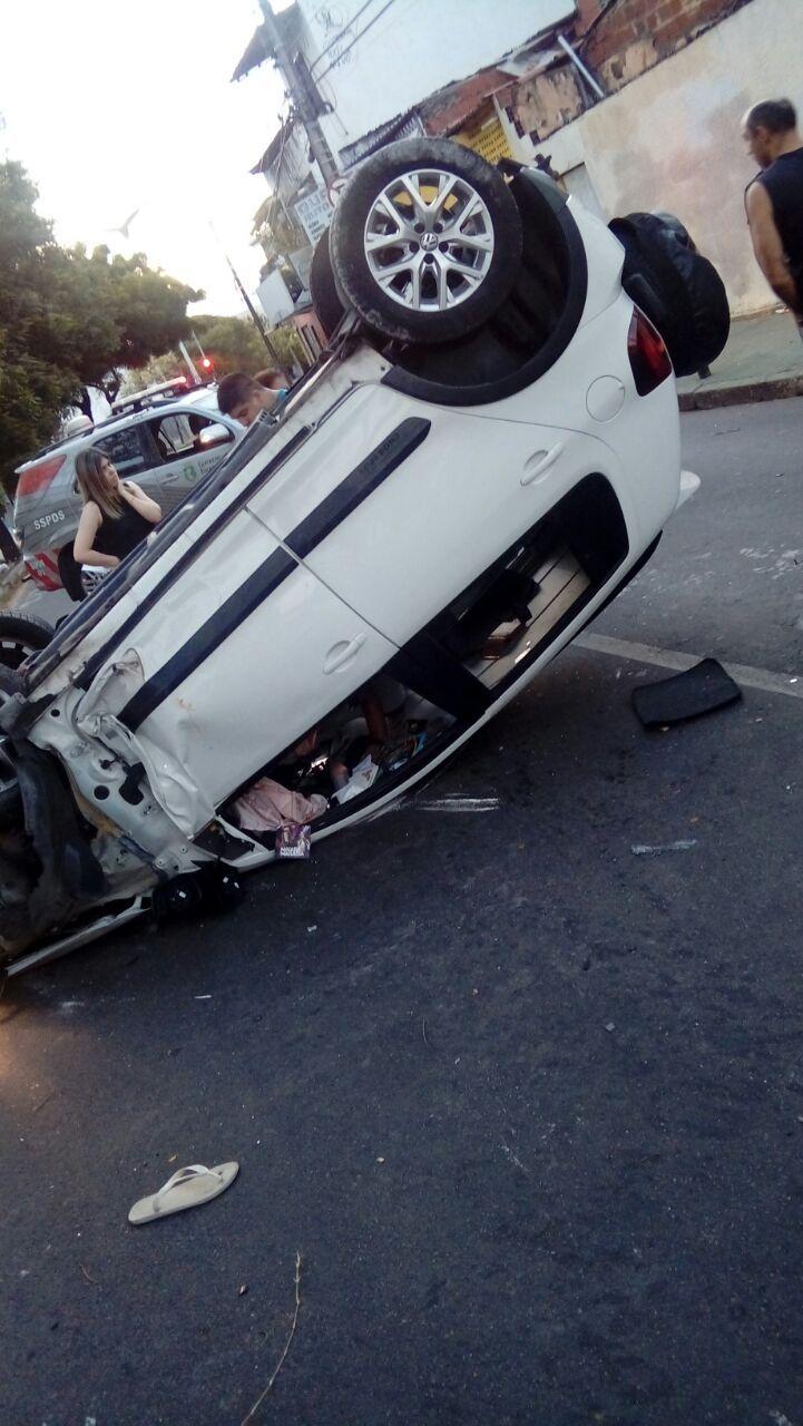 Um carro branco virado na esquina da avenida Jovita Feitosa e um carro da Polícia Rodoviária Estadual atrás