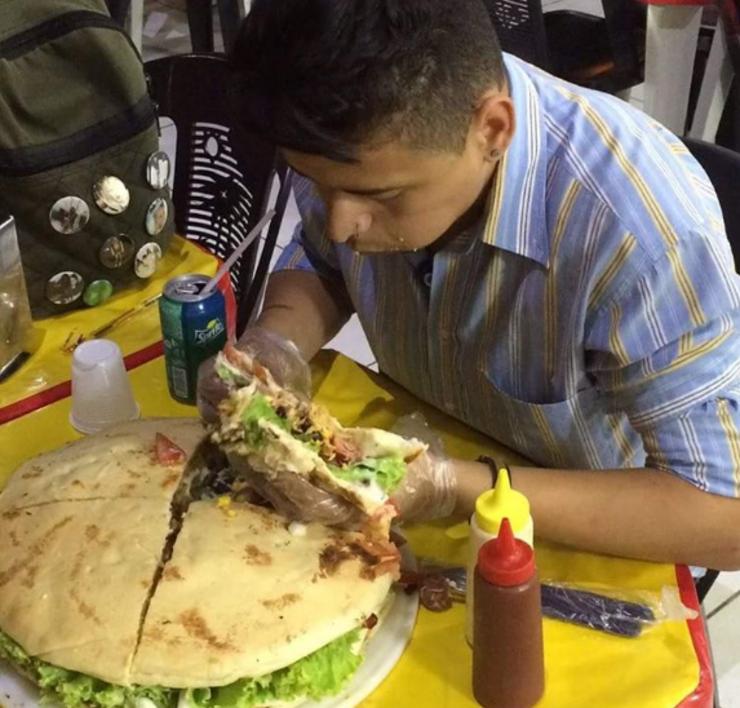 Cliete tentando comer o sanduíche de 4g.