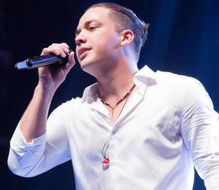Wesley Safadão com camisa branca, cantando em show