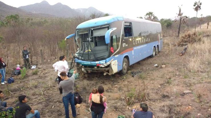 Ônibus com a frente destruída parado no barranco. Passageiros aguardam assistência.