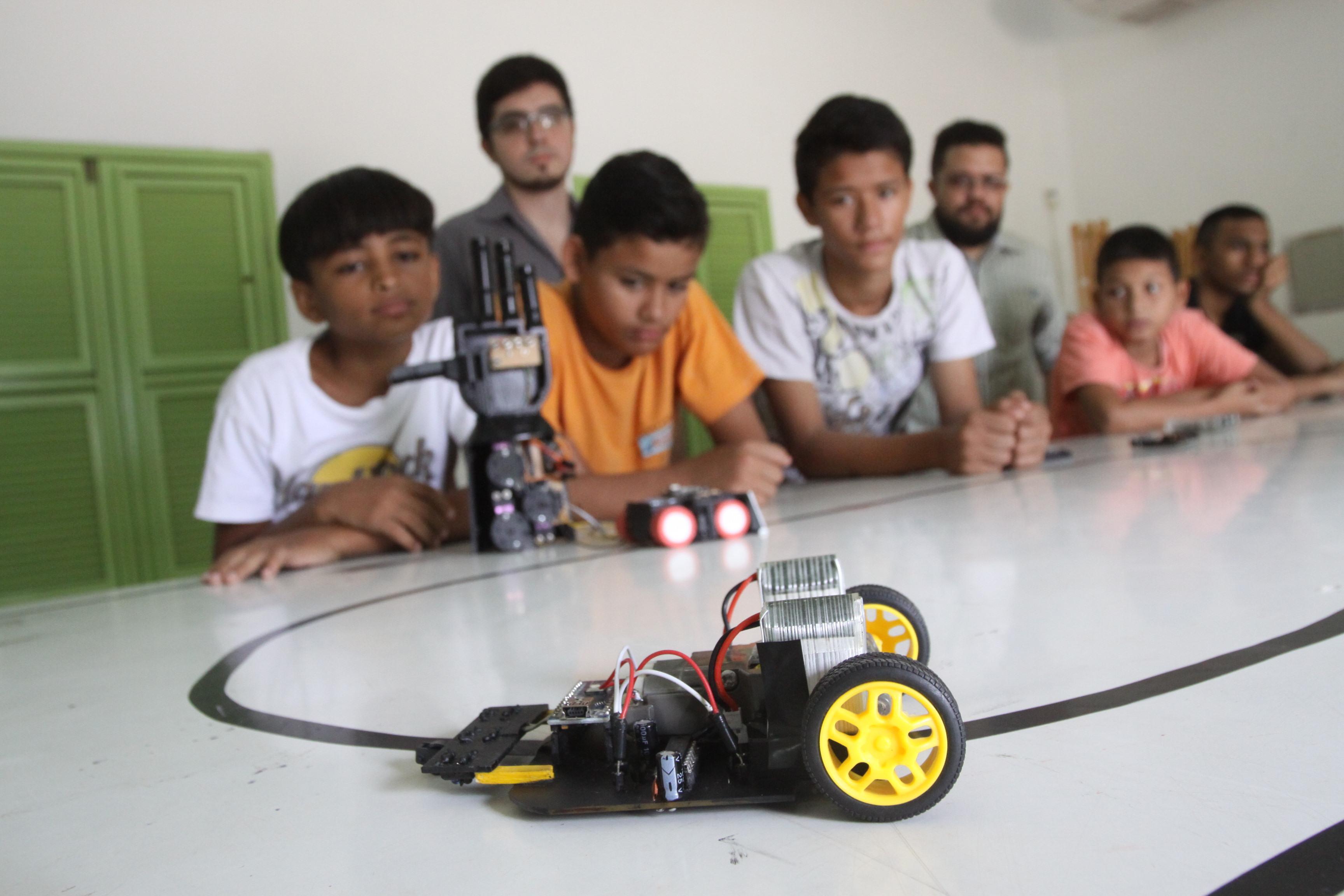 Seis crianças em volta de uma mesa, com um carrinho de brinquedo em cima, passando por um autopista