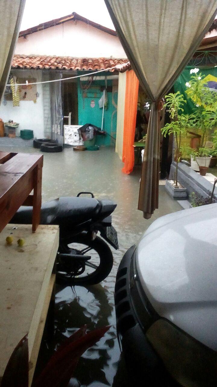 Um carro, uma moto e uma casa parecem na imagem com muita água no chão alagado