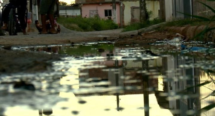 Foto de esgoto correndo sobre asfalto em rua