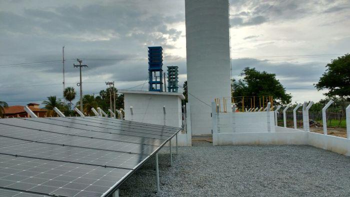Foto da usina de energia solar com 22 placas e do poço perfurado, logo atrás, com cerca de 60 metros