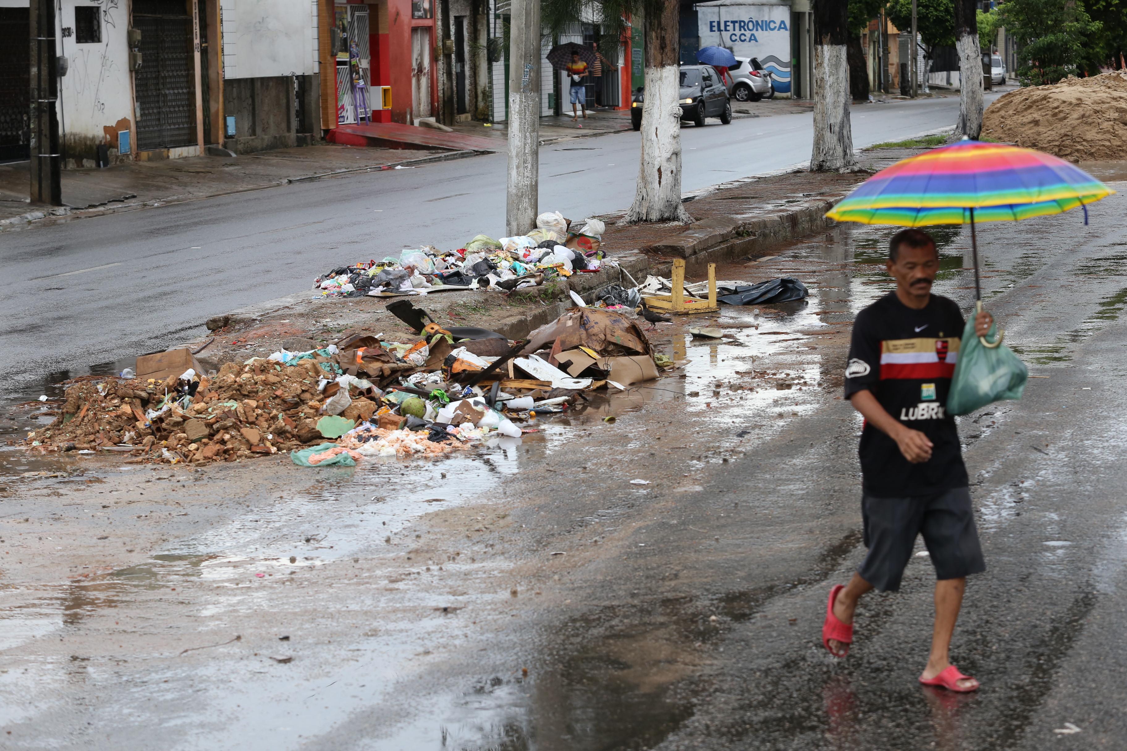 Um homem com guarda-chuva atravessa a avenida Leste Oeste, com o canteiro central cheia de lixo