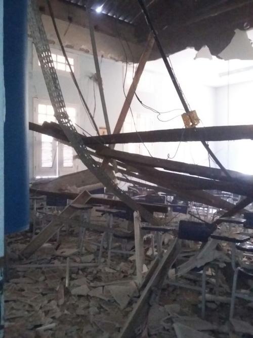Escombros do teto sobre mesas e carteiras
