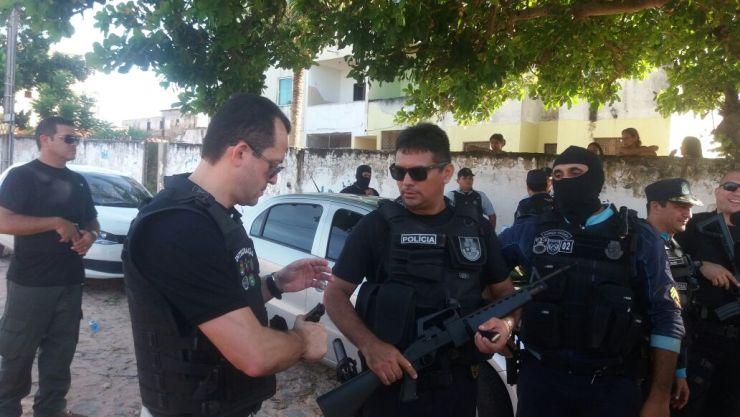 André Costa em pé, junto com policiais que participam da operação