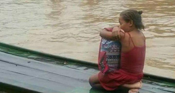 Menina Rivânia abraçada aos livros ao ser resgatada de enchente