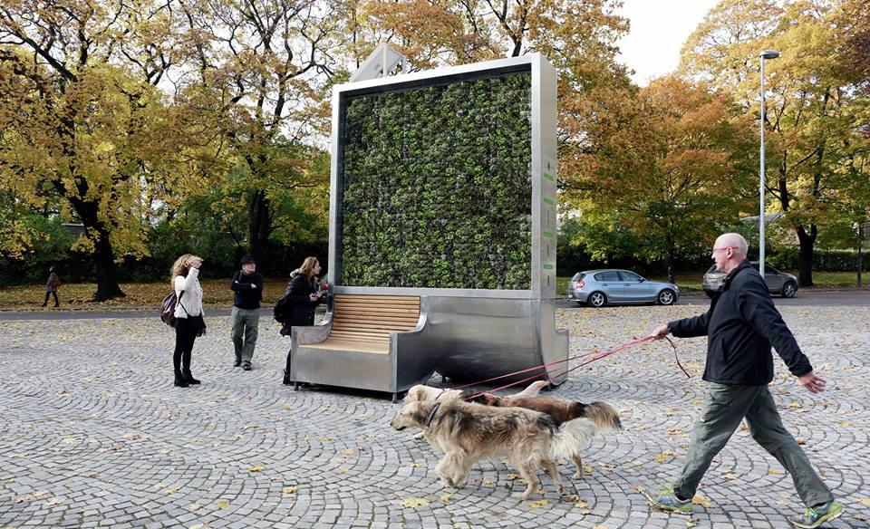 Imagem da CityTree em Oslo, na Noruega, com pessoas caminhando perto e interagindo com a instalação que também inclui um banco