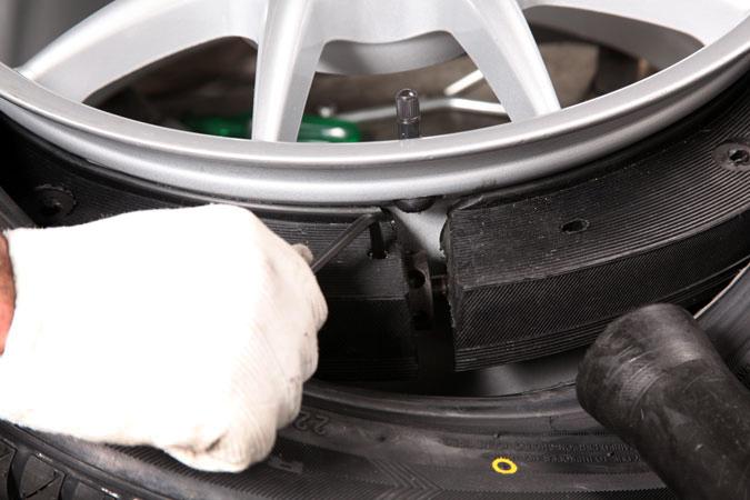Foto próxima de um pneu. Na imagem, aparece a mão de alguém segurança uma ferramenta junto ao pneu