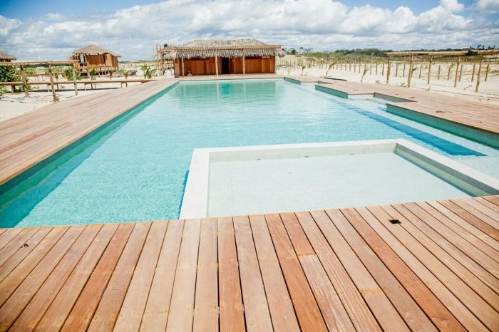 A imagem mostra uma grande piscina, cercada por um piso de madeira e em meio a areia branca de praia