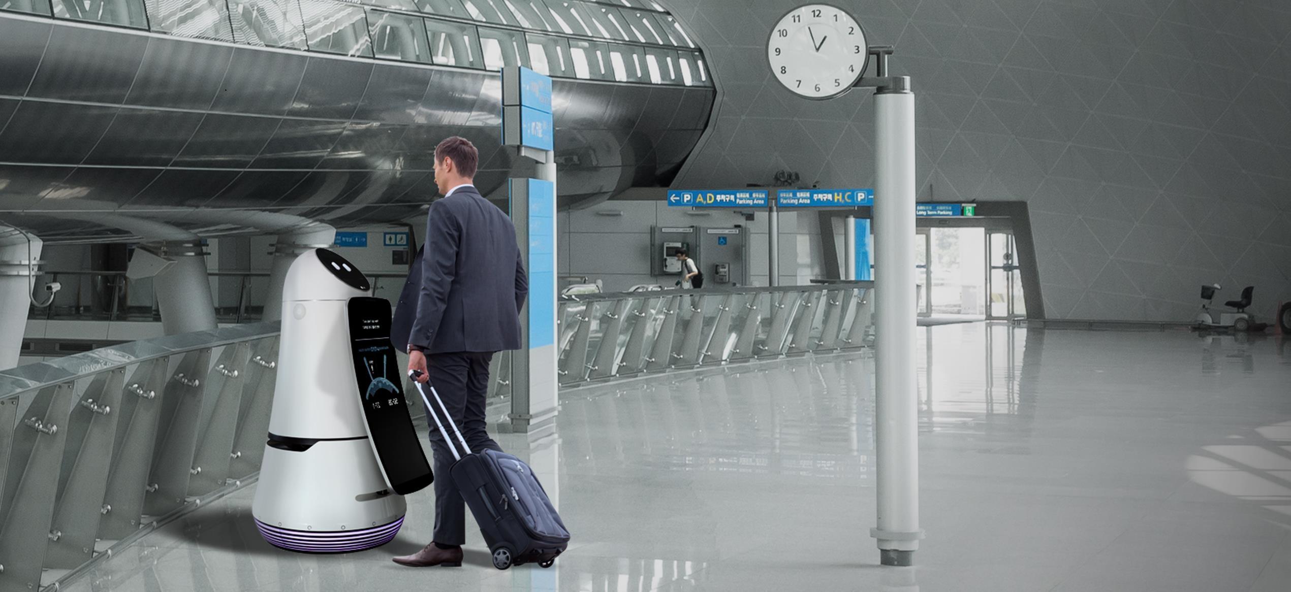 A imagem mostra um passageiro interagindo com o robô guia no meio do aeroporto