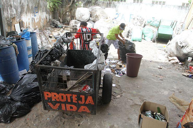 Na foto, catador segura carroça de ferro, dentro de associação