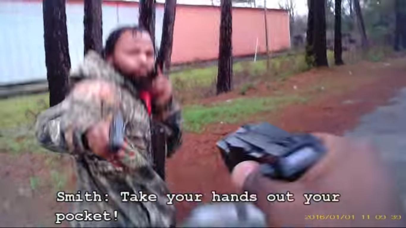 A imagem mostra o momento em que o policial, que estava filmando toda a abordagem com uma câmera embutida nos óculos, aponta um taser para o suspeito enquanto este aponta uma pistola, logo antes de disparar