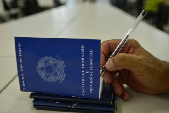 A imagem mostra uma pessoa escrevendo na carteira de trabalho