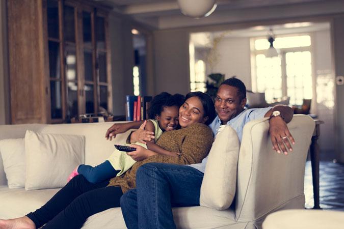 Pai, mãe e filha pequena estão sentados no sofá de uma bela casa, sorrindo.