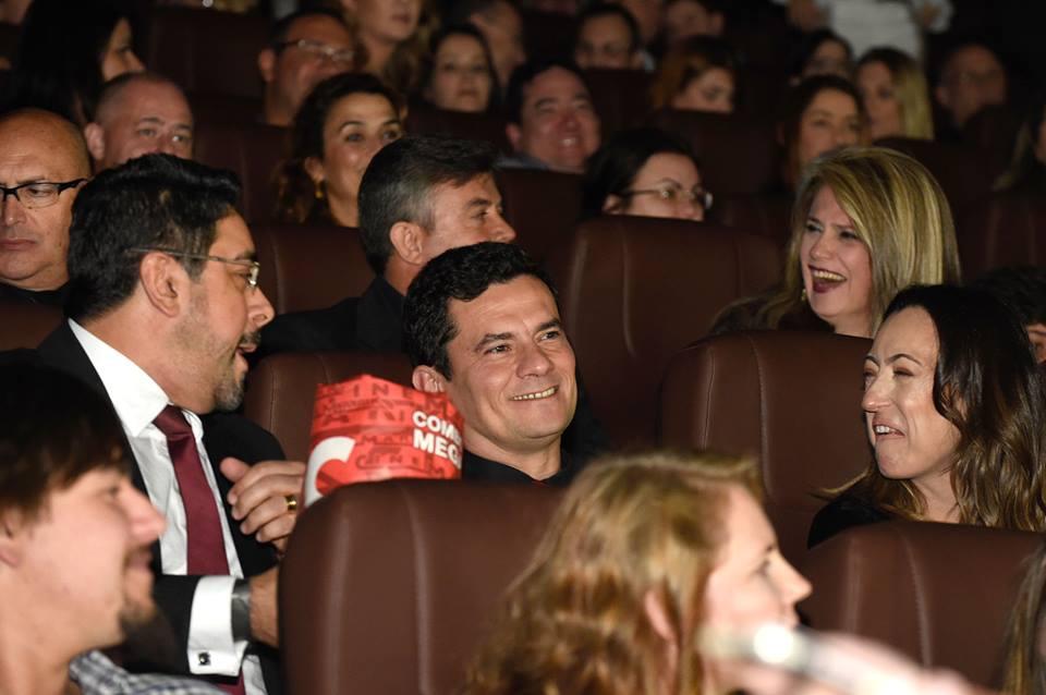 Sérgio Moro aparece no centro da imagem, ao lado da mulher, Rosângela e do colega Marcelo Bretas. Todos estão no cinema assistindo à primeira exibição do longa-metragem sobre a operação Lava Jato