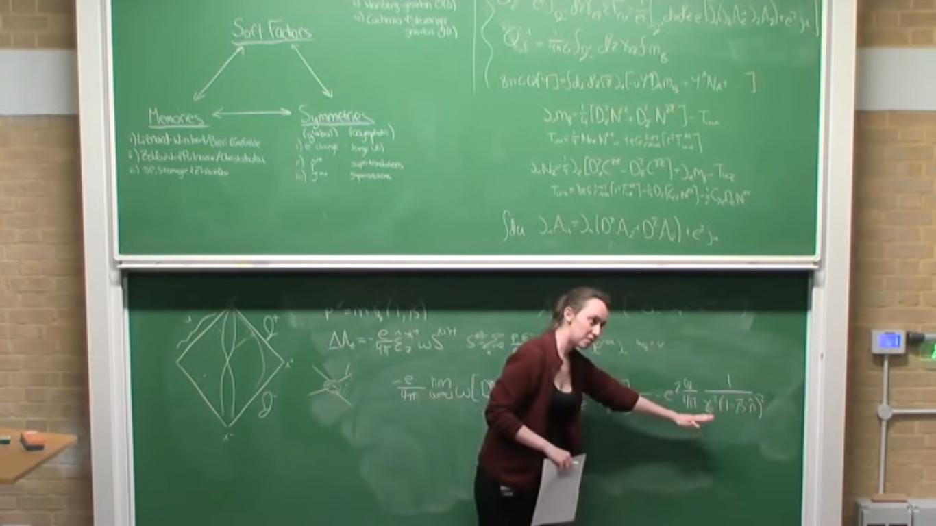 A imagem mostra Sabrina Gonzalez Pasterski enquanto escreve e discursa em um quadro negro