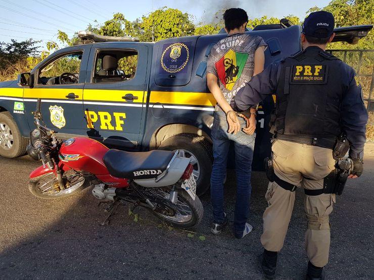Policial da PRF apreendendo adolescente e moto vermelha. Viatura da PRF no fundo