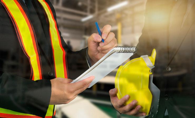 Oficial inspeciona fábrica, com um bloquinho de papel e uma caneta na mão, e conversa com homem de terno que segura um capacete