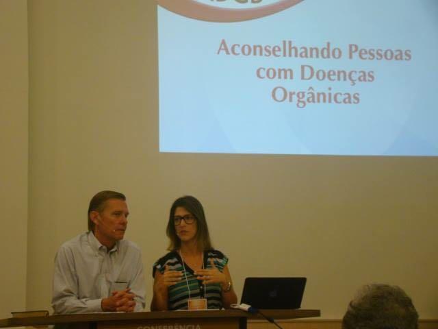 Homem e mulher em posição de apresentação de palestra