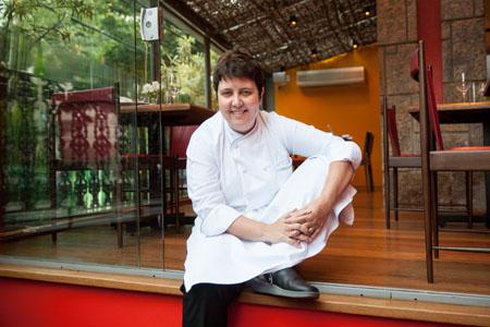 A chef Roberta Sudbrack sentada no chão de um restaurante
