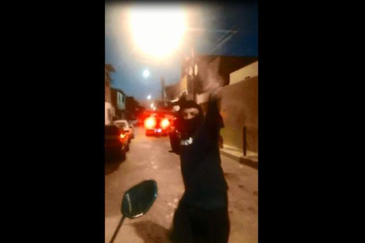 Suspeito armado faz sinal de vitória para a câmera