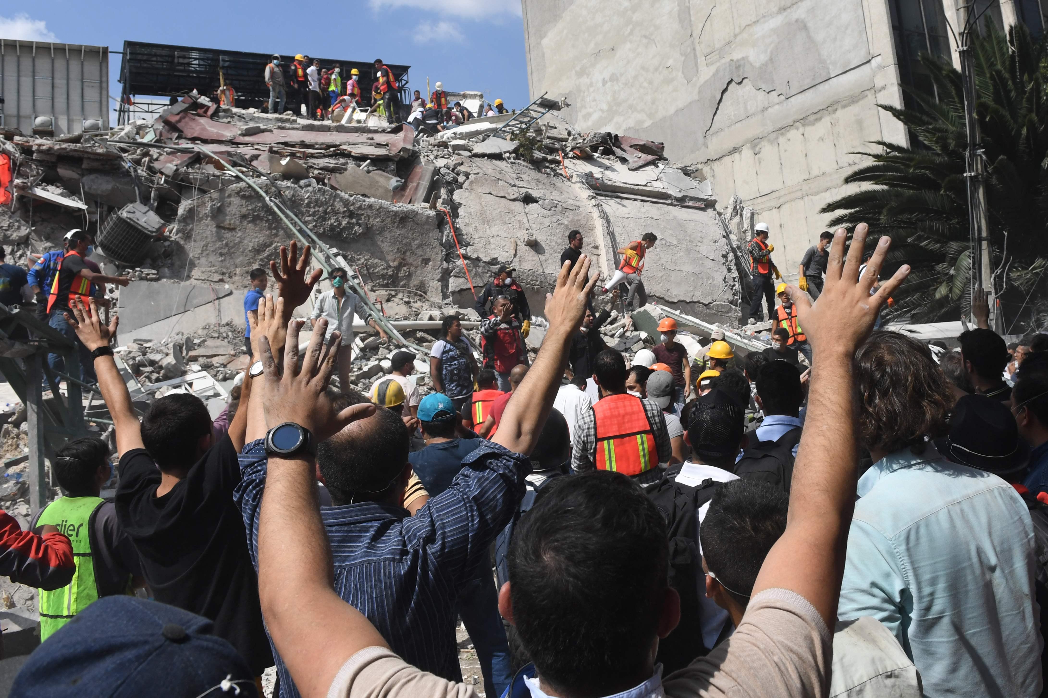 Pessoas realizando resgates em meios aos escombros