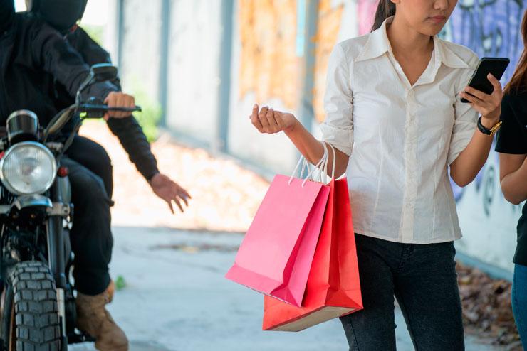 Uma mulher andando na rua com o celular em uma mão e sacolas no outro braço. Dois homens de moto estão atrás dela e um se prepara para puxar as sacolas