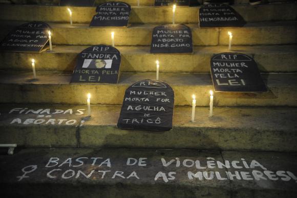 Tabletes pretos com palavras de luto por mulheres que morreram em decorrência da violência no Brasil
