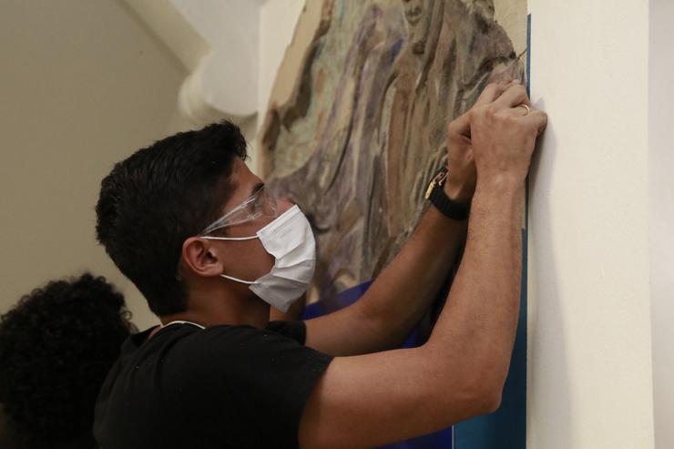 Estudante retira reboco com bisturi entre os relevos da escultura misteriosa