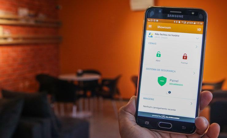 Mão segurando smartphone com aplicativo Smart Home, da Servis, e ao fundo o showroom para demonstração do uso do aplicativo