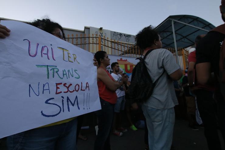 Mulher segura cartaz que diz: