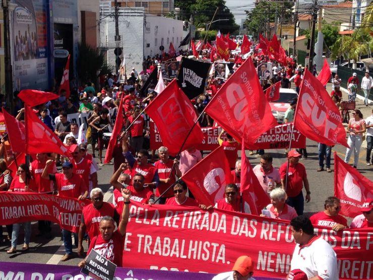 Manifestantes com camisas e faixas vermelhas