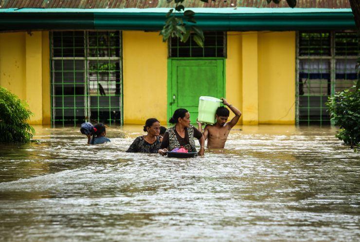 Moradores andando na água após tempestade
