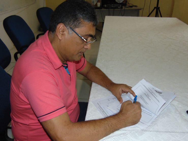 Prefeito de Aracoiaba, Antônio Cláudio Pinheiro, assinando decreto