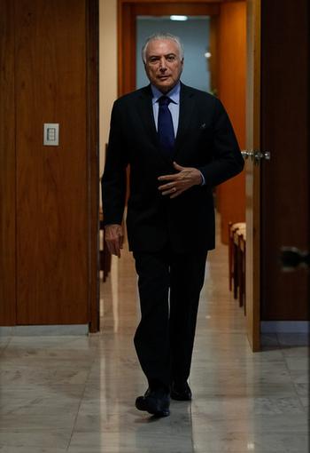 Foto de Michel Temer caminhando em direção à câmera, de terno