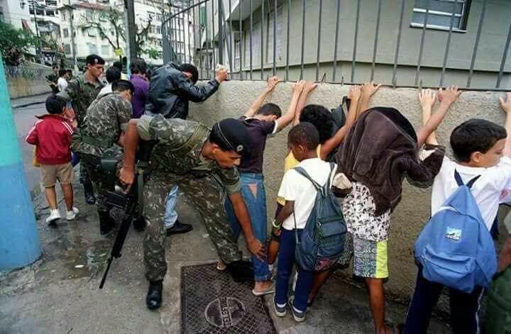 Foto de crianças enfileiradas, com mãos na parede, sendo revistadas por militares