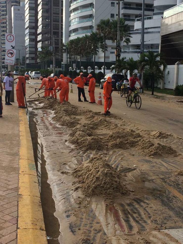 Trabalhadores retirando areia da pista da Beira Mar