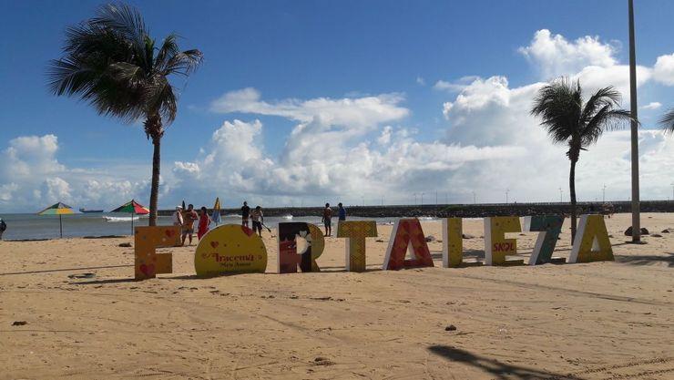 Letreiro com nome de Fortaleza parcialmente coberto pela areia