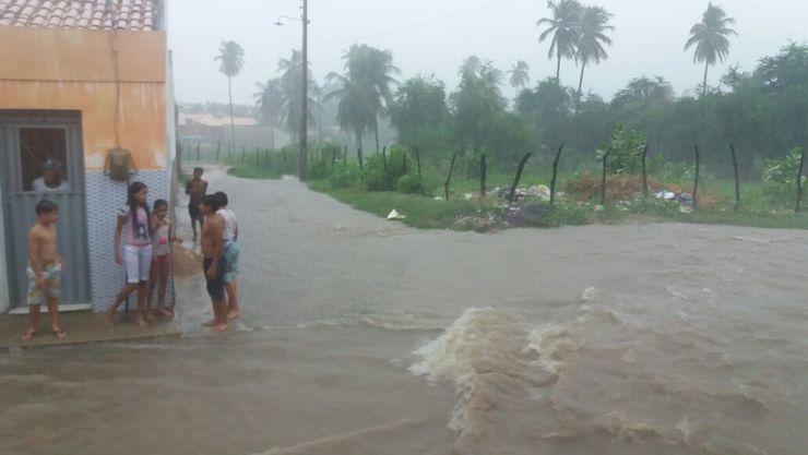 Imagem de pessoas observando rua alagada
