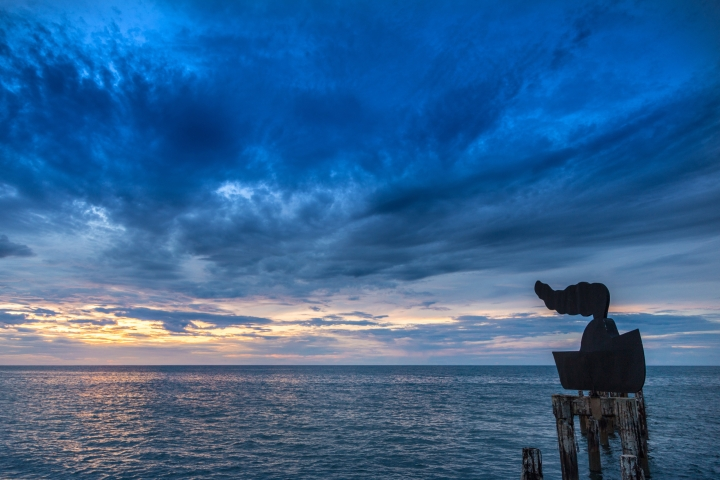 Foto da escultura em forma de barquinho, com o mar ao fundo