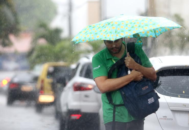 Homem se protege da chuva em uma avenida lotada de carros