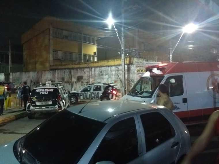 Cruzamento de ruas próximo à Praça da Gentilândia. Há um carro estacionado e a rua está interditada por um carro do Samu e um da PM