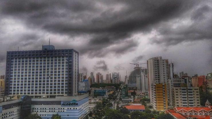Imagem mostra ceu nublado com nuvens carregadas. Abaixo há a foto de uma rua de Fortaleza e prédios