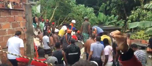 Populares e bombeiros durante resgate em área de desabamento