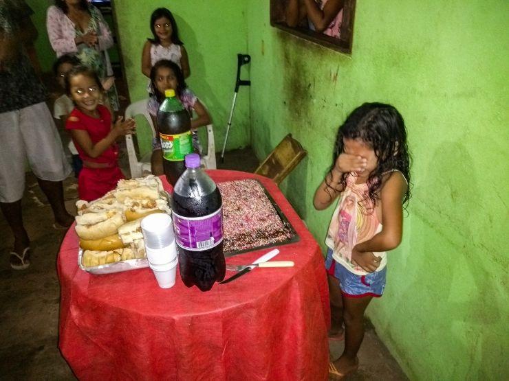 Menina emocionada com bolo de aniversário