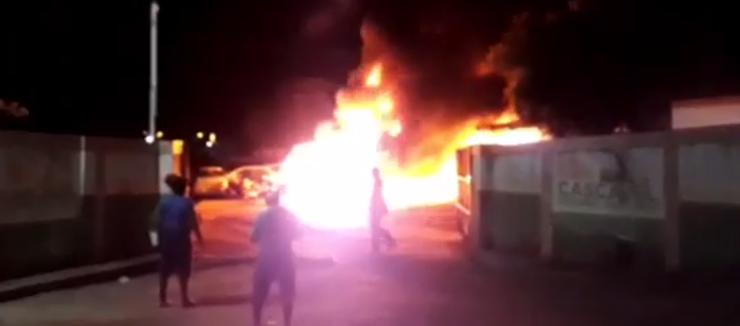 Frente de galpão onde motos e carros estão pegando fogo.