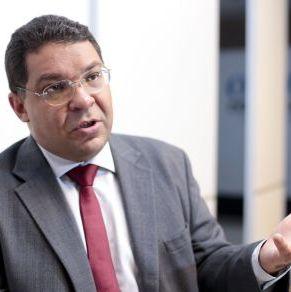 Foto de Mansueto Almeida, de terno, gravata e óculos, gesticulando enquanto fala